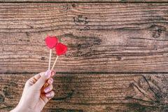 Frau ` s Hand, die zwei rote Herzen hält, formen auf Stock Dunkles hölzernes baskground Rote Rose und Inneres über Weiß Stockfoto