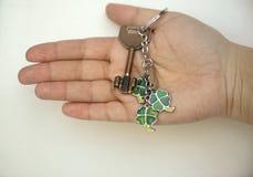 Frau ` s Hand hält einen Türschlüssel mit einem Kleeblattcharme Lizenzfreie Stockfotografie