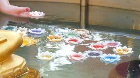 Frau ` s Hand lässt eine lodernde Wachskerze in Form einer Lotosblume in einem Teich fallen stock video