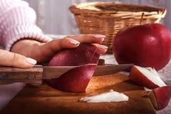 Frau ` s Hand mit einem Messer, das einen Apfel auf einem hölzernen Brett schneidet lizenzfreie stockbilder