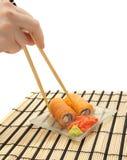 Frau ` s Hand mit Essstäbchen und maki Sushi Lizenzfreie Stockfotos