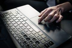 Frau ` s Hand unter Verwendung der Laptoptastatur stockfotografie