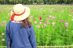 Frau ` s hinterer tragender Strohhut beim Betrachten des Blumengartens lizenzfreie stockbilder