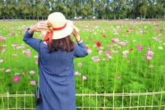 Frau ` s hinterer tragender Strohhut beim Betrachten des Blumengartens lizenzfreies stockfoto