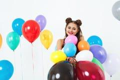 Frau in 60s, Kleidung der Art 70s, die mit bunten Ballonen aufwirft Lizenzfreies Stockbild