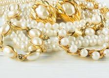 Frau ` s Schmuck Weinleseschmuckhintergrund Schöne Gold- und Perlenhalsketten, Armbänder und Ohrringe auf weißem Holz Flache Lage stockbilder