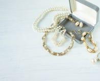 Frau ` s Schmuck Weinleseschmuckhintergrund Schöne Gold- und Perlenhalsketten, Armbänder und Ohrringe in einer Geschenkbox auf we stockfotografie