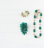 Frau ` s Schmuck Weinleseschmuckhintergrund Smaragdbrosche, Halskette und Ohrringe des schönen hellen Bergkristalls auf Weiß flac lizenzfreie stockfotos