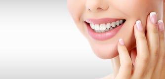 Frau ` s toothy Lächeln gegen einen grauen Hintergrund lizenzfreies stockfoto