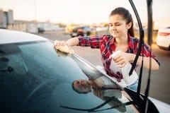 Frau s?ubert vorderes Glas des Autos mit Spray lizenzfreie stockfotografie
