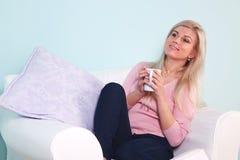 Frau saß in einem trinkenden Tee des Lehnsessels Stockfotografie