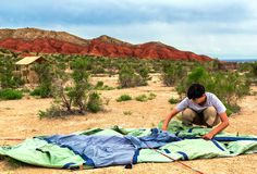 Frau sammelt Zelt auf einem Hintergrund von Bergen lizenzfreie stockfotos
