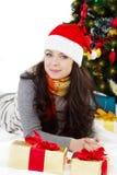 Frau in Sankt-Hut, der unter Weihnachtsbaum liegt lizenzfreies stockfoto