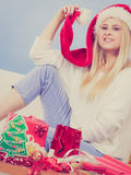 Frau in Sankt-Hut, der Weihnachtsgeschenke vorbereitet Stockfoto
