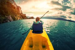 Frau schaufelt Kajak im See mit Türkiswasser lizenzfreie stockfotos