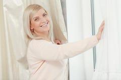 Frau schaut aus dem Fenster heraus Lizenzfreies Stockfoto