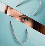 Frau schaut durch Einkaufstasche Lizenzfreies Stockbild