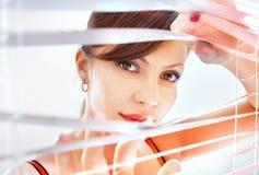 Frau schaut durch Jalousie Lizenzfreies Stockbild