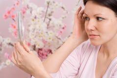 Frau schaut im Spiegel Stockfotos