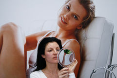 Frau schaut im Spiegel Lizenzfreie Stockbilder