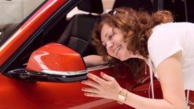 Frau schaut im Spiegel des Autos Stockfotos