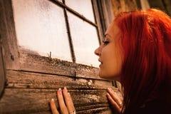 Frau schaut neugierig im Fenster des alten Hauses Lizenzfreie Stockfotos
