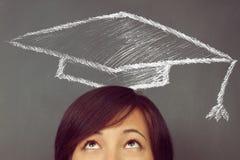 Frau schaut oben auf dem Zeichnen des pädagogischen Hutes Lizenzfreie Stockfotografie
