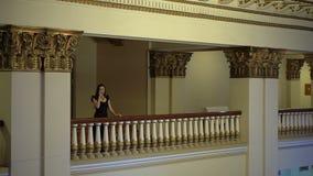 Frau schaut unten vom Balkon und trinkt Wein stock footage