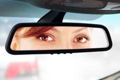 Frau schaut zum Rückspiegel Stockbild