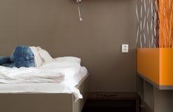 Frau schläft auf Bett im Hotelzimmer Stockbild