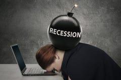 Frau schläft auf Laptop mit Rezessionsbombe lizenzfreies stockbild