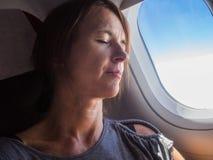 Frau schläft in den Flugzeugen stockfotos