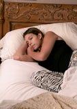 Frau schlafend in ihrem Bett Stockbild