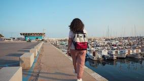 Frau schlendert allein auf Meer-pearce mit vielen privaten Booten in der Morgenzeit stock video