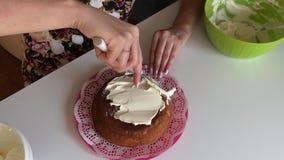 Frau schmiert Schwammkuchen mit Sahne Tragen Sie eine Schicht Creme auf allen Seiten auf stock video footage
