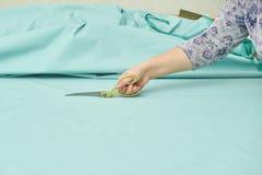 Frau schneidet blaues Material mit goldenen Scheren stockfoto