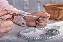 Frau schneidet das Band mit Scheren und macht Dekorationen stockfoto