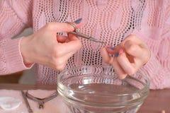Frau schneidet Häutchen mit scissor Macht Maniküre selbst Nahaufnahmehände stockfotografie