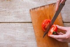 Frau schneidet rote Tomate auf Teilen Lizenzfreie Stockbilder