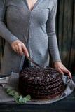 Frau schneidet Schokoladenkuchenabschluß Dunkle Töne lizenzfreies stockfoto