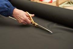 Frau schneidet schwarzes Material mit goldenen Scheren lizenzfreie stockbilder