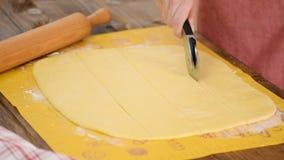 Frau schneidet Teig für backendes Messer, der Teig, der auf Tabelle liegt stock footage
