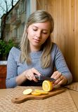 Frau schneidet Zitrone Lizenzfreie Stockbilder