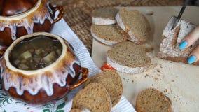Frau schnitt in Brot In der Nähe gibt es ein mageres Lebensmittel in einem Topf stock video