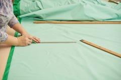 Frau schnitt materiellen grünen Bleistift für Kleidung heraus stockfoto