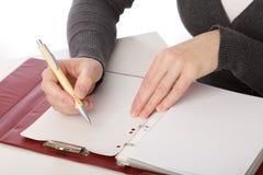 Frau schreiben durch Feder auf Papier stockbild