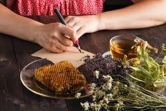 Frau schreiben Rezept des Kräutertees lizenzfreie stockfotos