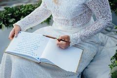 Frau schreibt auf ein Papier Stockbild
