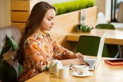 Frau schreibt bedacht auf ihrem Laptop lizenzfreies stockbild