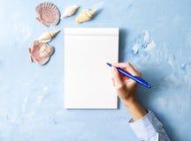 Frau schreibt in Notizbuch auf blaue Steintabelle, Spott oben mit Rahmen der Muschel, die Draufsicht und plant Feiertag durch Mee lizenzfreie stockfotos
